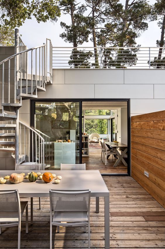 un piccolo terrazzo con una zona pranzo - semplici mobili in metallo per pranzare e zucche come runner da tavolo