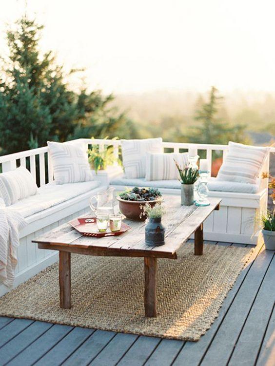 un piccolo terrazzo scoperto con una grande panca imbottita a forma di L con contenitore, un tavolo in legno e un tappeto di iuta