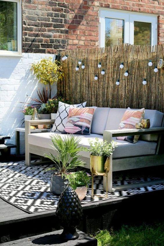 un piccolo terrazzo con un grande e comodo divano, luci su di esso e molta vegetazione in vaso e fiori