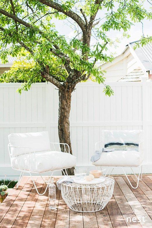 un piccolo terrazzo scoperto con un albero vivente, mobili bianchi semplici ed eleganti e un tavolino per servire i pasti