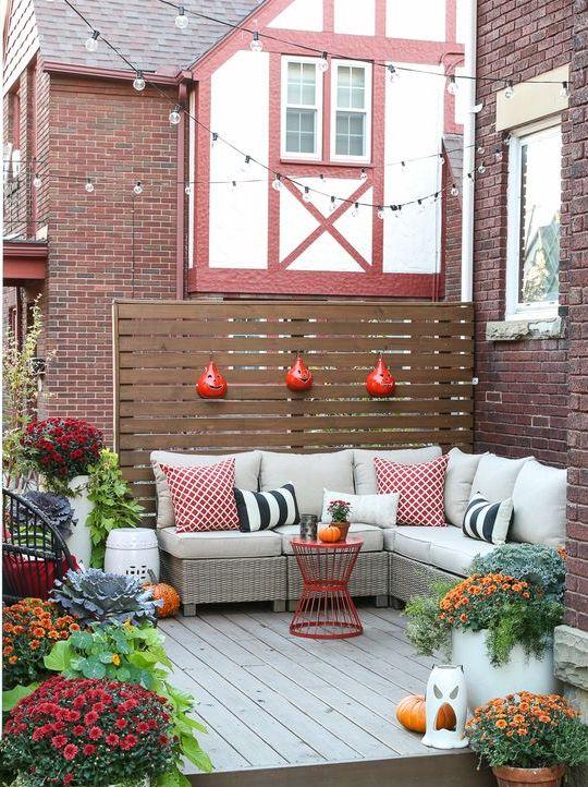un piccolo terrazzo di ispirazione autunnale con una panca imbottita a forma di L, cuscini colorati e fiori in vaso