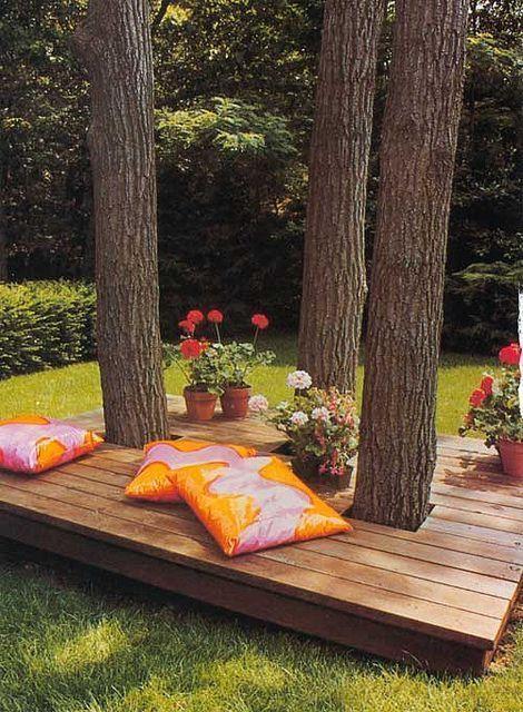 un piccolo terrazzo scoperto con alberi viventi, vegetazione in vaso e fiori e cuscini colorati è un magnifico rifugio rilassante
