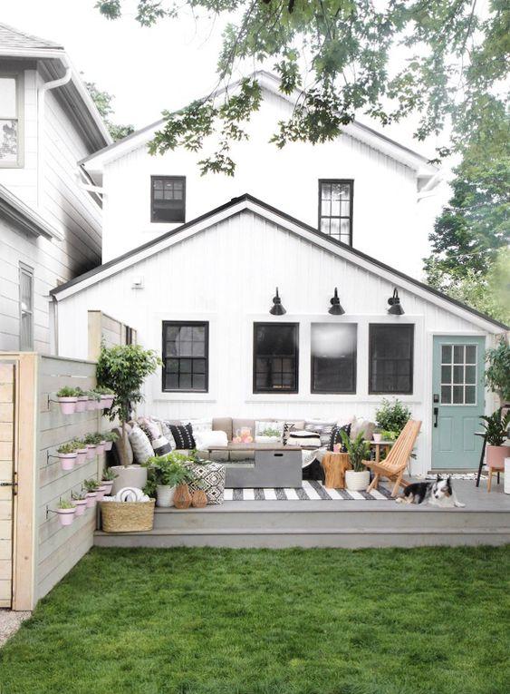 un piccolo terrazzo scoperto con un divano componibile, piante in vaso, una cassapanca, un tappeto e alcune sedie pieghevoli
