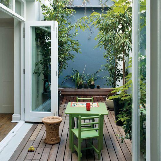 un piccolo terrazzo con mobili verdi, piante in vaso e un tavolino in rattan sembra molto accogliente e appartato