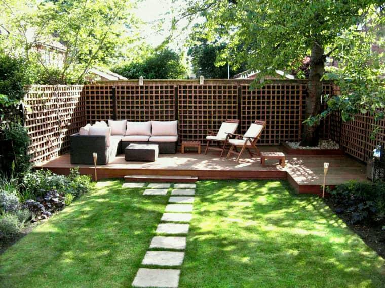 un piccolo terrazzo scoperto con mobili contemporanei: un divano, un tavolino da caffè, alcune sedie pieghevoli e sgabelli intorno