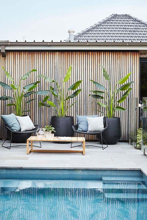 una piscina coperta piastrellata con un tavolo di legno, alcune sedie in rattan con cuscini e piante in vaso in fioriere nere