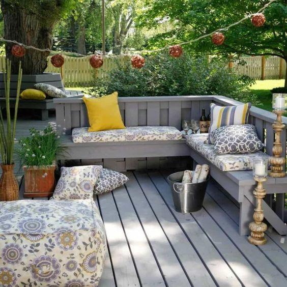 un piccolo terrazzo esposto alle intemperie con una panca a forma di L incorporata, cuscini e cuscini stampati, un po 'di verde in vaso