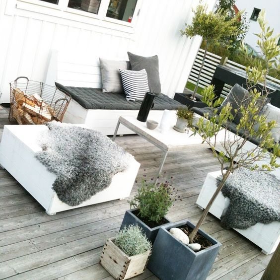 un piccolo terrazzo di legno esposto alle intemperie con mobili contemporanei, vegetazione in vaso e fiori e schermo per la privacy