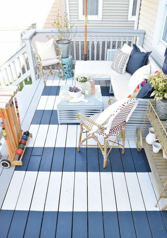 un piccolo terrazzo scoperto a strisce con mobili in rattan, una panca a forma di L con cuscini, piante in vaso e un tavolino blu