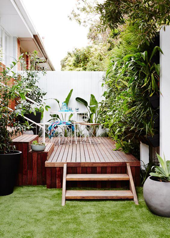 un piccolo terrazzo in legno colorato con semplici mobili in metallo e compensato e molta vegetazione intorno per la freschezza