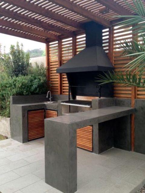 un'area barbecue minimalista di cemento scuro e legno, con una griglia e un lavandino più un piano di lavoro in cemento per mangiare