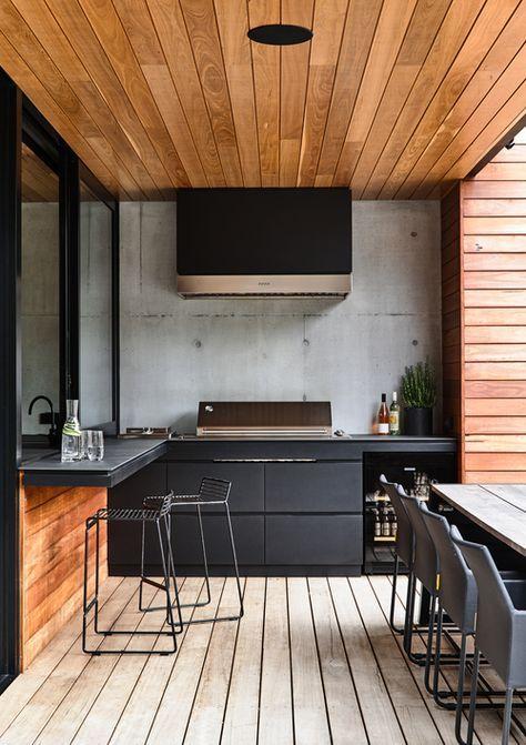 cucina barbecue all'aperto contemporanea realizzata in legno nero e tinto, con armadi opachi, una griglia, una cappa e alcuni spazi per i pasti