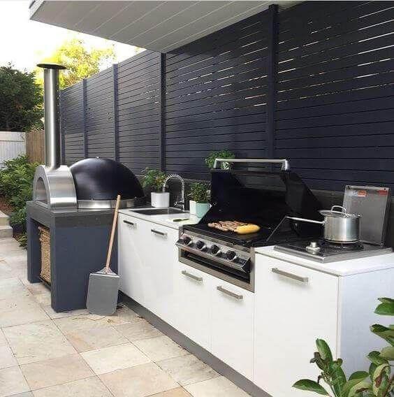 cucina barbecue all'aperto contemporanea realizzata in bianco e nero, con un forno per pizza e una griglia più armadietti