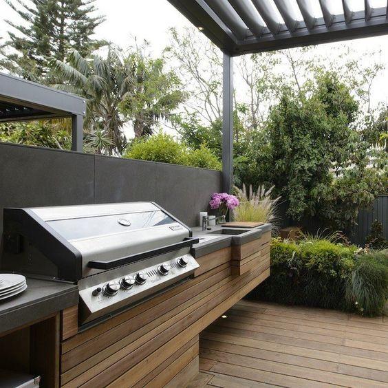 cucina da esterno con barbecue minimalista di assi di legno e un piano di lavoro in cemento più una griglia