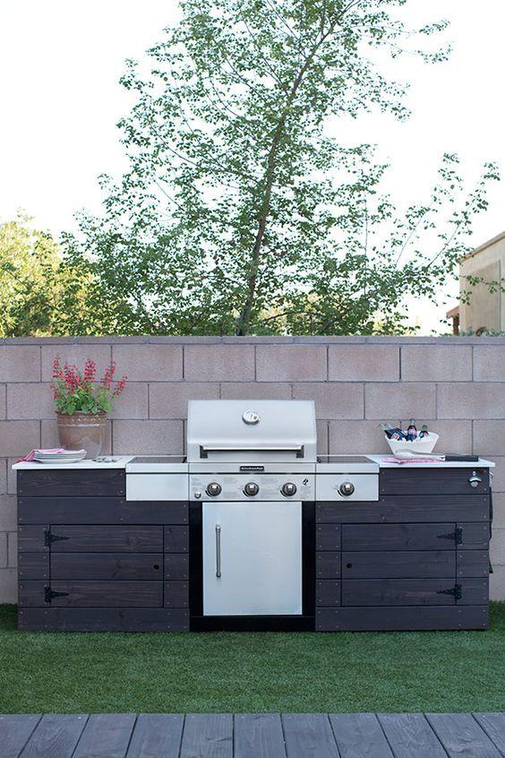una rustica cucina all'aperto in legno tinto scuro, con una grande griglia e un po 'di spazio per cucinare