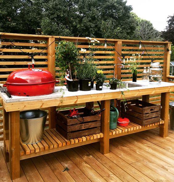cucina da esterno con barbecue rustica rilassata in legno e cemento, con molte erbe aromatiche in vaso e una griglia più spazio di archiviazione aperto