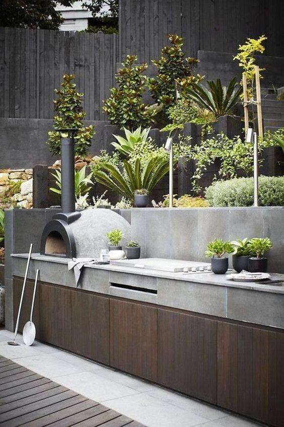 cucina barbecue all'aperto minimalista in legno e cemento, con grill, forno per pizza e vegetazione in vaso