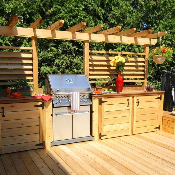 una rustica cucina all'aperto in legno tinto chiaro, con molto spazio per cucinare e una grande griglia