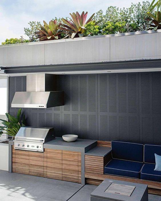 cucina da esterno con barbecue minimalista in cemento, legno e metallo con una zona cottura, una griglia con cappa e una zona salotto