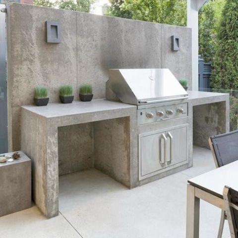 una zona grill all'aperto minimalista di cemento, con una griglia e una vegetazione in vaso per rinfrescare lo spazio