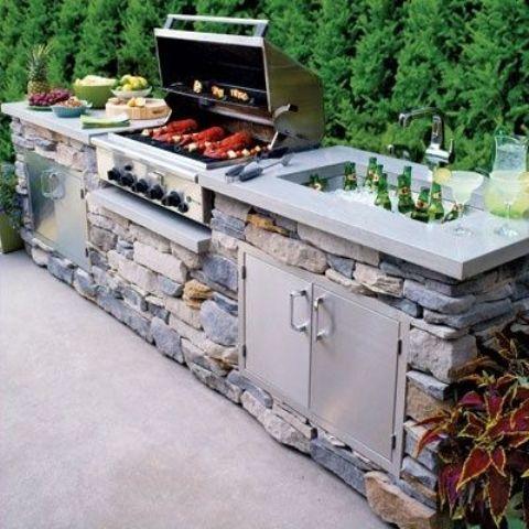 una tradizionale cucina all'aperto con un mobile in pietra, un piano di lavoro in cemento, una griglia, una zona cottura e un refrigeratore per bevande