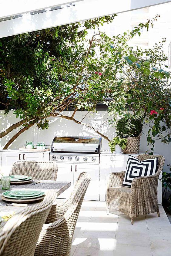 un'accogliente cucina all'aperto con grill e angolo cottura più una zona pranzo con mobili in vimini