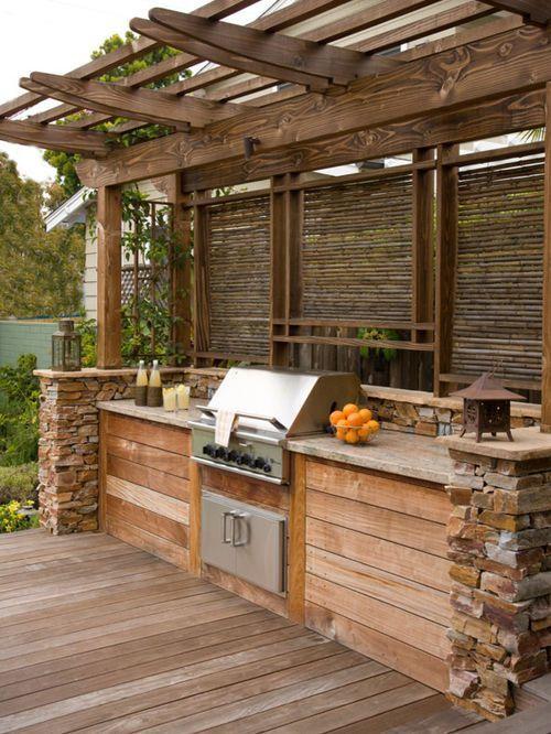una rustica cucina all'aperto costruita in legno e pietra, con un piano di cottura e una griglia più lanterne intorno