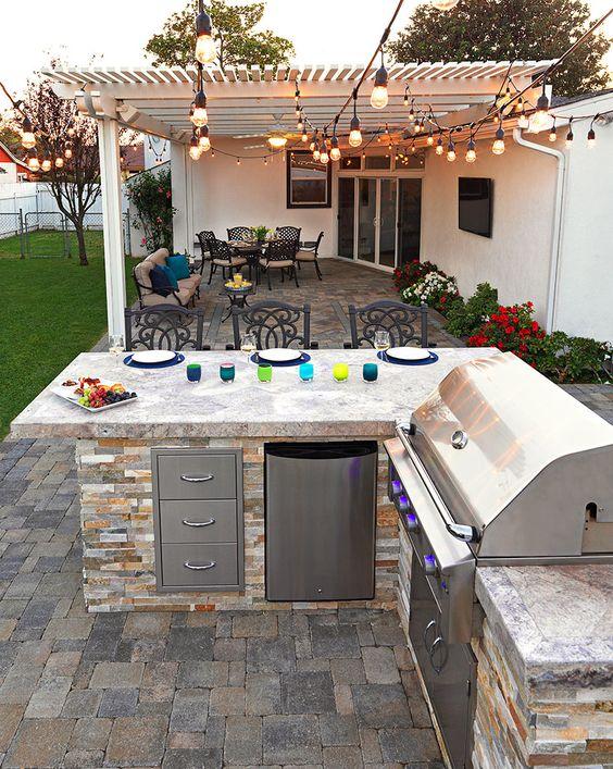 una semplice cucina esterna rustica costruita in pietra, con ripostigli e una griglia più una zona pranzo
