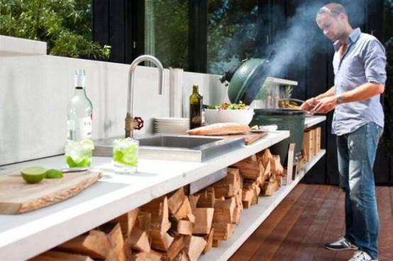una moderna cucina esterna con legnaia, lavello, zona cottura e grill