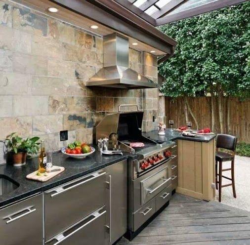 un'elegante cucina esterna moderna con armadi in metallo, ripiani neri e una griglia più una cappa