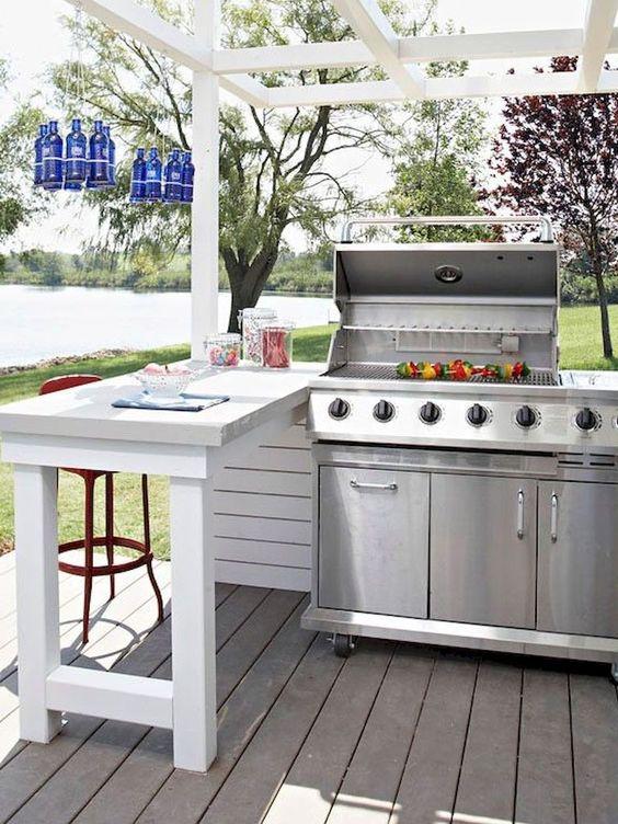 un'accogliente area barbecue all'aperto con una grande griglia, uno spazio per mangiare al suo fianco e bottiglie blu sopra di esso