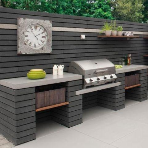 un'elegante area barbecue esterna in blocchi di cemento modulare, con un ampio spazio di cottura e una griglia più un orologio