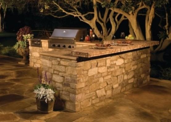 una semplice cucina esterna rivestita in pietra e con piani di lavoro più una griglia per cucinare