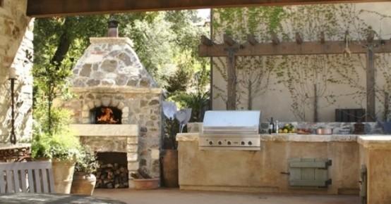 una tradizionale cucina all'aperto in pietra con grill e forno a legna più verde intorno
