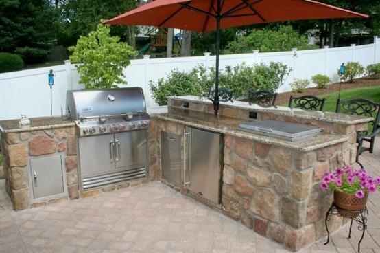 una cucina all'aperto semplice ed elegante costruita in pietra e metallo con una griglia, un dispositivo di raffreddamento e piani di cottura