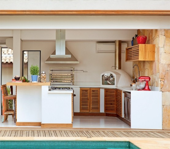 una cucina esterna minimalista con armadi bianchi e ante in legno, una cappa e una griglia più uno spazio aggiuntivo per mangiare