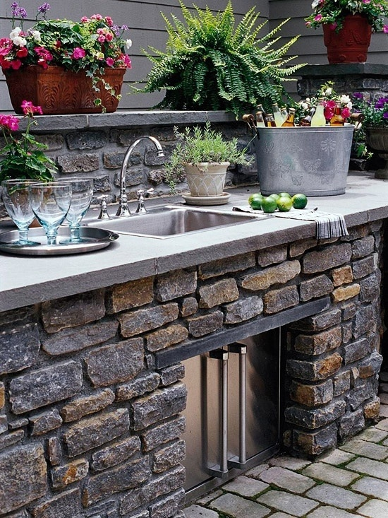 una cucina tradizionale con pietra, mattoni e un mobile contenitore con ante in metallo, un lavandino e piante e fiori in vaso