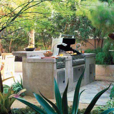 una cucina esterna in cemento e metallo con griglia e piano rialzato per consumare i pasti