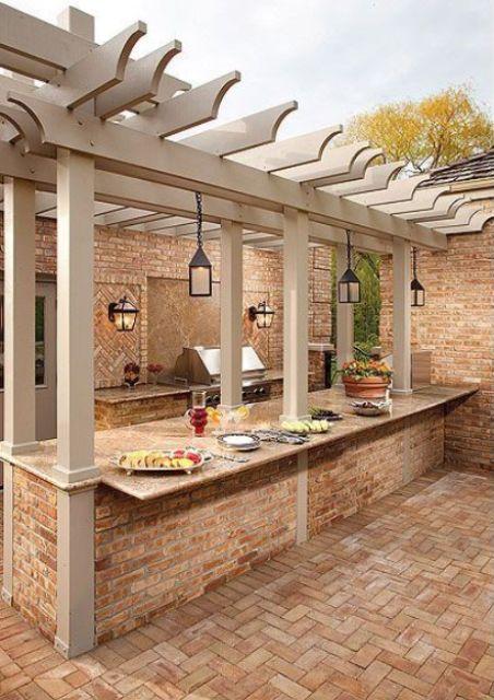 una zona barbecue all'aperto costruita in pietra e mattoni, con una griglia, lanterne, un piano di cottura e uno spazio per i pasti