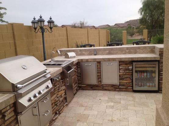 un'area barbecue all'aperto in pietra e piastrelle, con piano cottura, lavello e grill