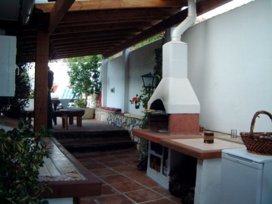 una zona cottura esterna con piano cottura e focolare per cucinare
