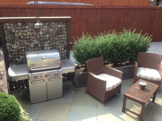 una semplice area barbecue all'aperto con una griglia, un paio di sedie e un tavolino da caffè più vegetazione intorno