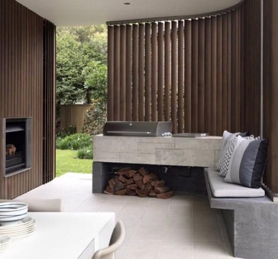 un'area barbecue minimalista con un piano di lavoro in cemento che scorre in una panchina, con una griglia in cima e un po 'di legna da ardere sotto