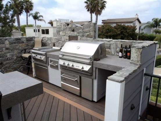 una cucina esterna costruita in pietra, cemento e metallo con fornello e griglia per cucinare comodamente