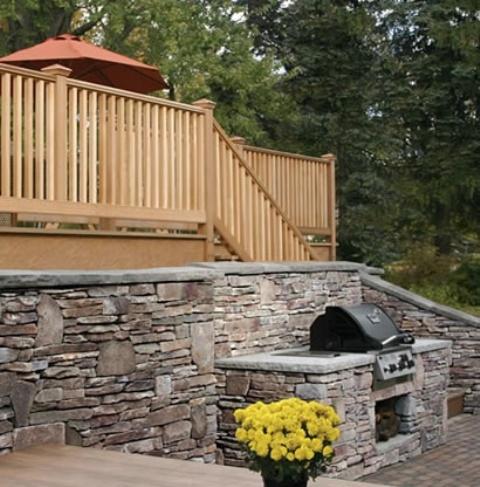 una tradizionale zona barbecue all'aperto con un muro in pietra e un bancone barbecue più una griglia e un tavolo per mangiare