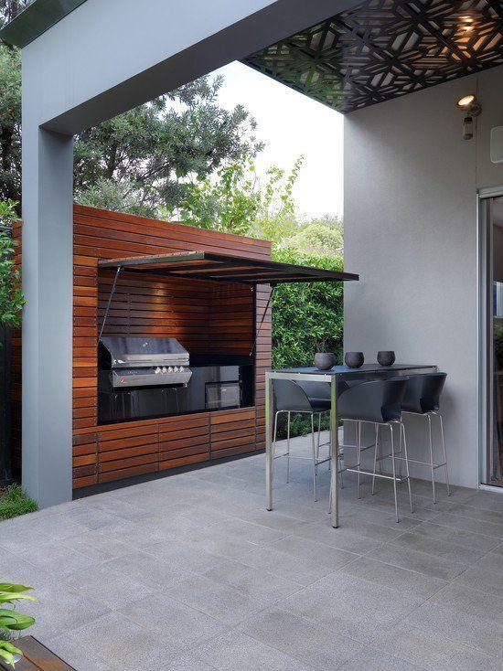 un'area barbecue esterna minimalista con un set da pranzo in nero e una griglia e un fornello all'interno di un mobile in legno