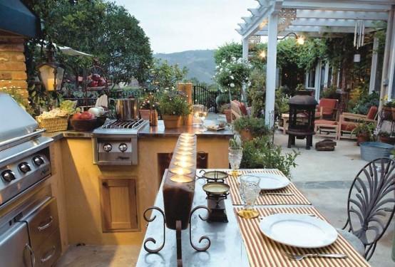 un'elegante zona grill all'aperto in cemento, con una griglia, un piccolo fornello e un po 'di spazio per cucinare più uno spazio per i pasti