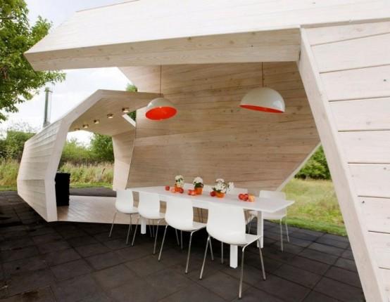 una zona pranzo minimalista all'interno di un padiglione scultoreo con luci e un elegante set da pranzo minimal in bianco