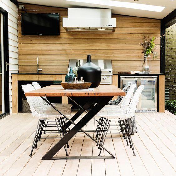 una sala da pranzo contemporanea con un accattivante tavolo con gambe a zig-zag, sedie in rattan bianco e una griglia accanto
