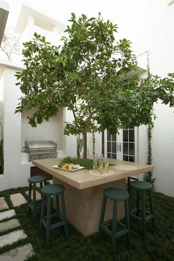 una stravagante sala da pranzo all'aperto con un tavolo in pietra e un albero vivace al suo interno più sgabelli verde scuro e una griglia accanto ad essa